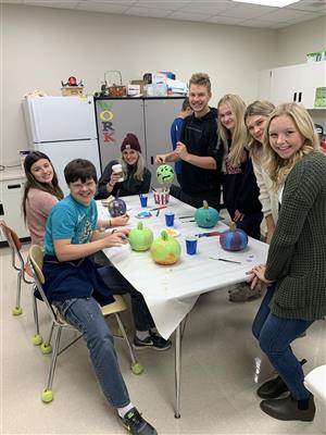 Special education students at Elk River High team with their Elk Buddies at last Halloween's pumpkin painting party.