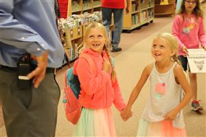 Two girls greet a teacher at Zimmerman Elementary School.